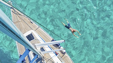 Man swimming by yacht