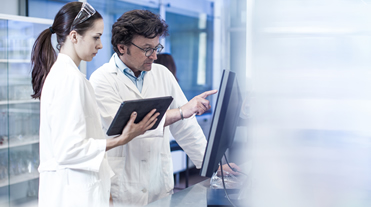 People in labcoats at work in lab